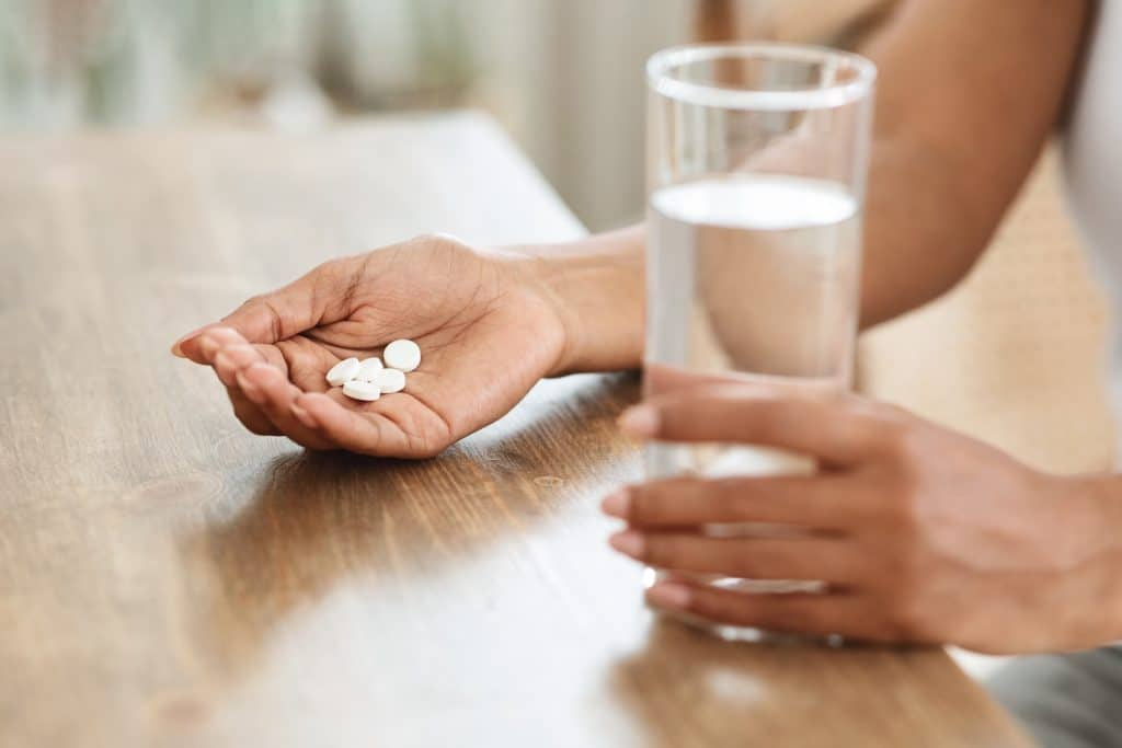 Dietary Supplements. Unrecognizable Woman Taking Pills And Drinking Water At Home, Cropped Image, Closeup