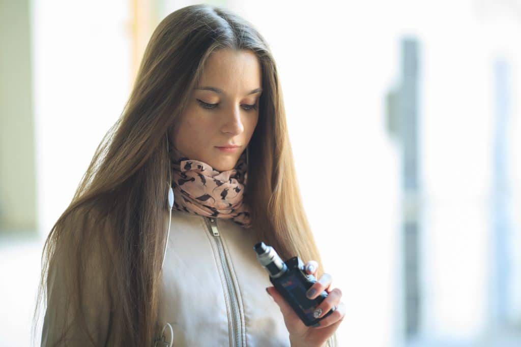 Vape teenager. Young pretty white girl in casual clothing smoking an electronic cigarette on the street in the spring.
