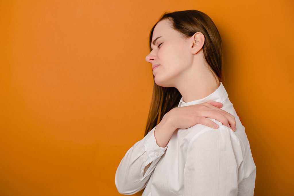 Tired unhappy young woman massaging hurt stiff neck isolated on brown studio background, fatigued sad girl rubbing tensed muscles to relieve joint shoulder pain, fibromyalgia concept. Selective focus