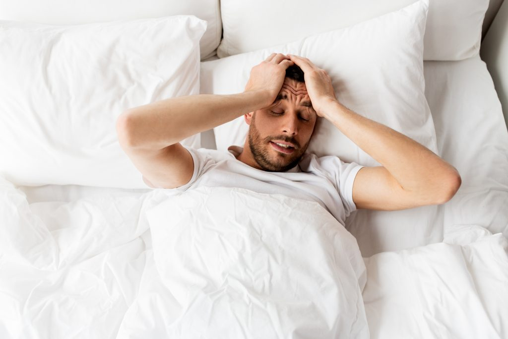 man lying in bed at home suffering from headache or hangover